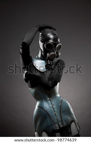 Woman in latex corset and gas mask, studio shot on black background - stock photo