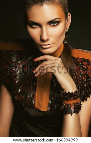 woman in leather accessory with orange make-up - stock photo