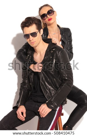 woman in leather jacket pulling the collar of her seated man from behind on white studio background