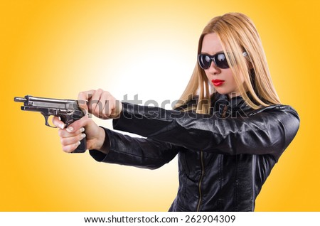 Woman in leather suit with handgun - stock photo