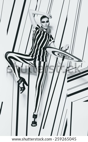 woman in leggings and striped top on striped background in studio - stock photo