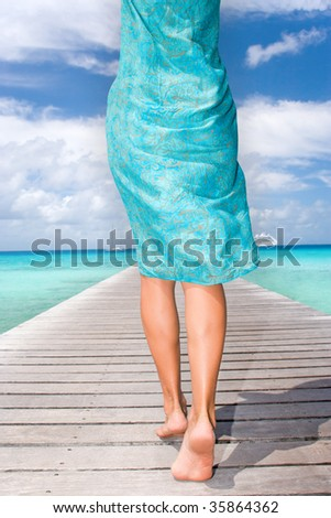 woman in light blue sarong waling on pier