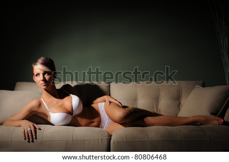 Woman in Lingerie Classic Beauty lying on a sofa with Text Space above - stock photo