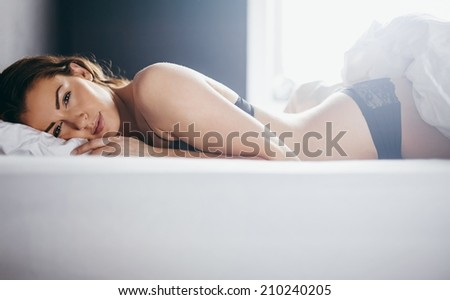 Woman in lingerie lying in her bed looking at camera. Beautiful young woman relaxing in bedroom. - stock photo