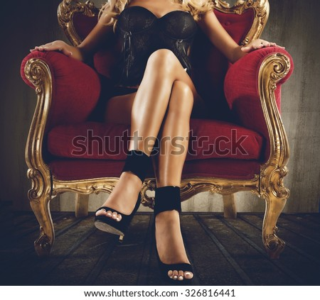 Woman in lingerie sitting on an armchair - stock photo