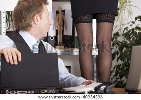 woman in lingerie standing on a stool - astound man looking at her legs - stock photo