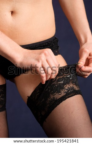 Woman in lingerie wearing black erotic stockings