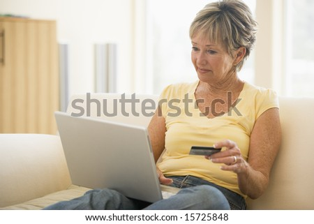 Woman in living room with laptop and credit card smiling - stock photo