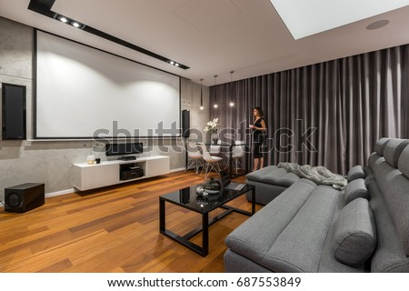 Woman In Living Room With Projector Screen Gray Sofa And Black Coffee Table