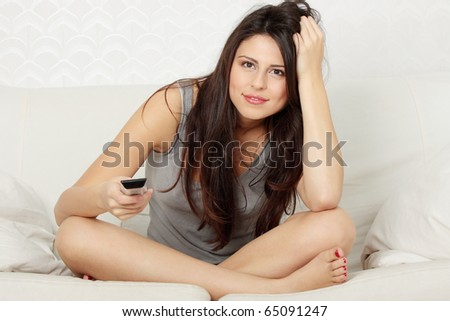 Woman in living room with remote control watching tv - stock photo