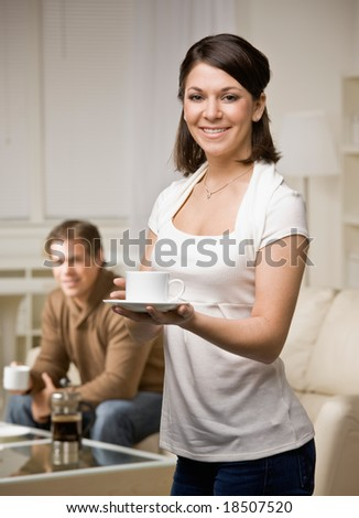 Woman in livingroom with husband holding coffee cup - stock photo
