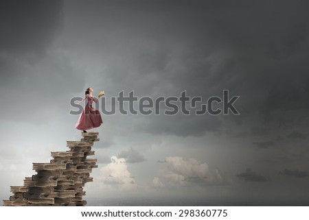 Woman in long dress with book in hand - stock photo