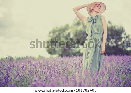 Woman in long green dress and hat in a lavender field  - stock photo
