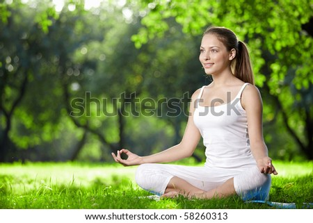 Woman in lotus pose in the park - stock photo