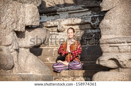 Woman in lotus pose with hands in Namaste gesture sitting near Shore temple, Mamallapuram, Tamil Nadu, India - stock photo