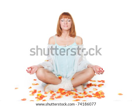 Woman in lotus position sitting on the floor on a white background