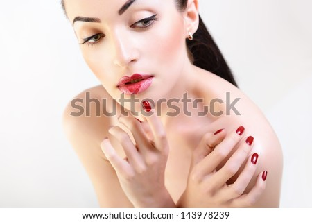 Woman in love. Beautiful girl with creative makeup with heart on her lips posing at studio over white background - stock photo