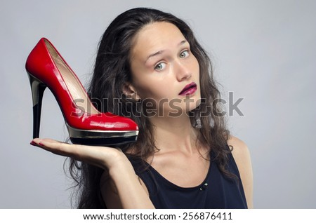 Woman in love with her high heel shoes. Beautiful girl holding her red sexy stiletto shoe. Lady shopping for shoes - stock photo