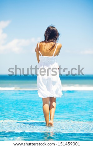 woman in luxury resort near swimming pool - back view - stock photo