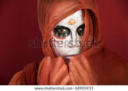 Woman in makeup for Day of the Dead with a scarf around her face