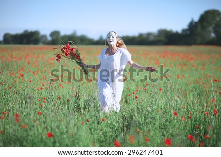 Woman in mask and white dress with poppies in hand running through a field - stock photo