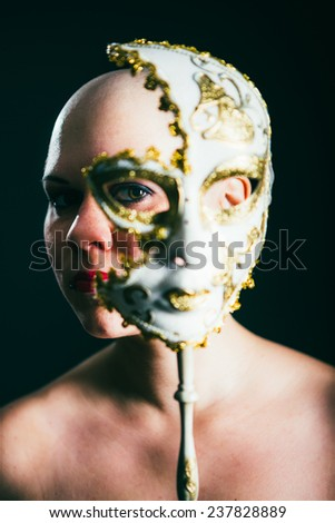 woman in masquerade mask at black background - stock photo