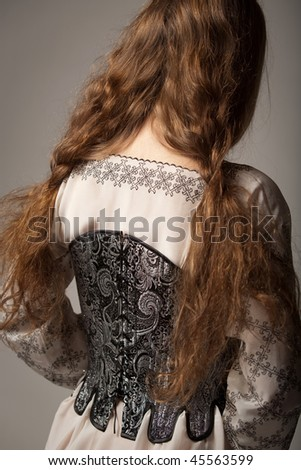 Woman in medieval corset and shirt on gray background - stock photo