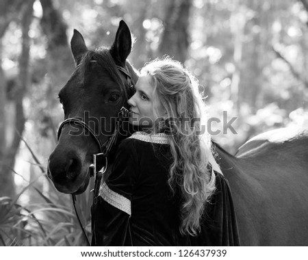 woman in medieval dress in forest with horse - stock photo