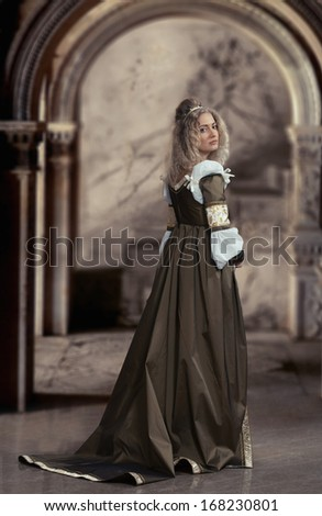 Woman in medieval dress looking back, antique interior background - stock photo
