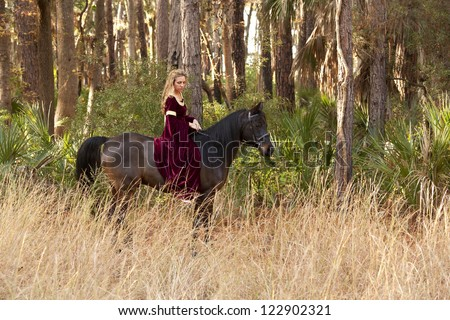 woman in medieval dress riding bareback through forest - stock photo