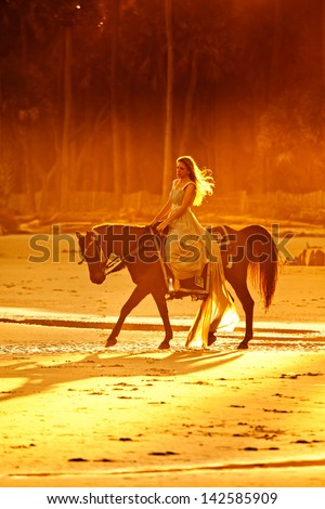 woman in medieval dress riding horse on beach at sunset - stock photo