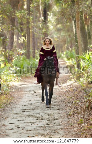 woman in medieval dress riding horseback through forest - stock photo
