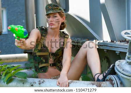 Woman in military camouflage shoots from a water pistol on the industrial background - stock photo
