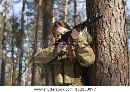 Woman in military uniform in the woods - stock photo