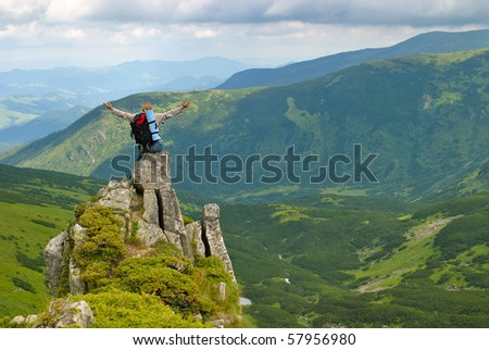 Woman in montains  on rock with back pack with his arms splayed and say: I love this world - stock photo