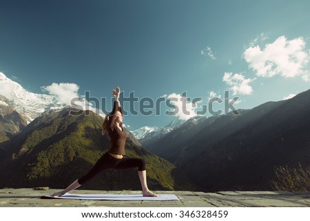 Woman in mountains doing yoga exercise outdoor. Sports lifestyle, Himalayas, snow capped peaks - stock photo
