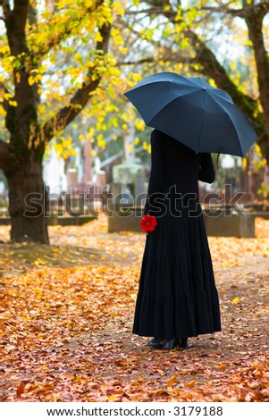 Woman in Mourning at Cemetery in Fall, with Black Umbrella - stock photo