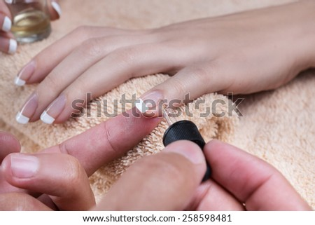 Woman in nail salon is receiving manicure by beautician. Applying the oil - stock photo