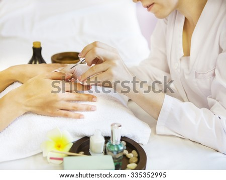 Woman in nail salon receiving manicure by beautician. Close up of female hands resting on white towel