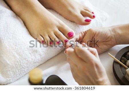 Woman in nail salon receiving pedicure by beautician. Close up of female feet resting on white towel - stock photo