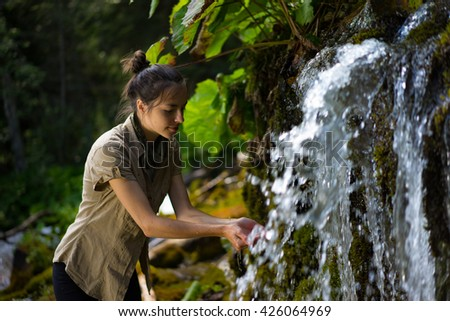 woman in nature, washing her hands or drinking water at the waterfall - stock photo