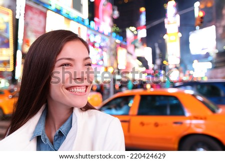 Woman in New York City, Manhattan, Times Square at night. Smiling happy joyful Multiethnic Asian Caucasian young urban professional in her 20s. - stock photo