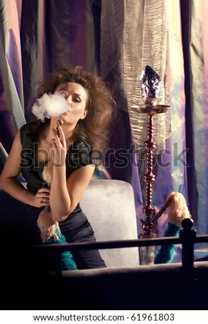 Woman in nightclub with hookah - stock photo