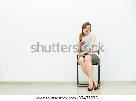 woman in office outfit sitting in a chair with some sheets of paper in hand and thinking - stock photo