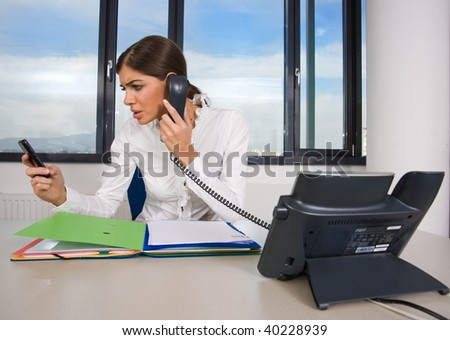 woman in office with documents talking on the phone - stock photo