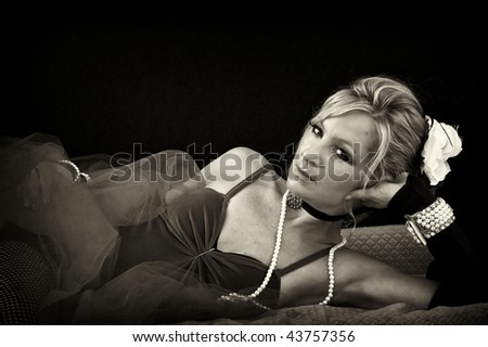 woman in old fashioned sexy outfit laying down looking at viewer, finished in sepia. - stock photo