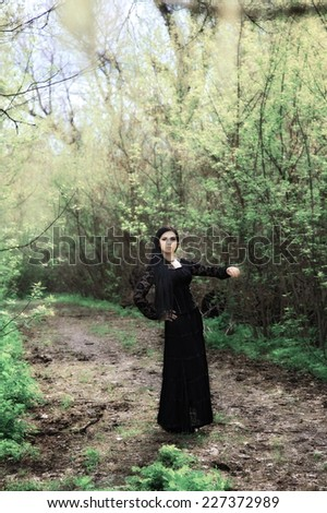 woman in old style black dress. outdoor shot