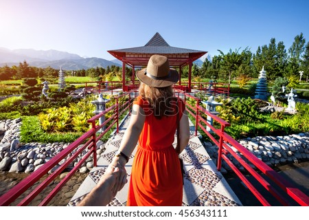 Woman in orange dress and hat holding man by hand going to Japanese Garden with pagoda