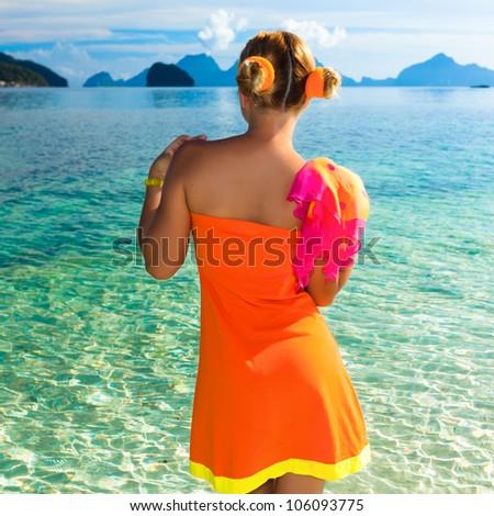 Woman in orange dress on the tropical beach - stock photo
