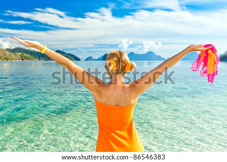 Woman in orange dress with raised hands - stock photo